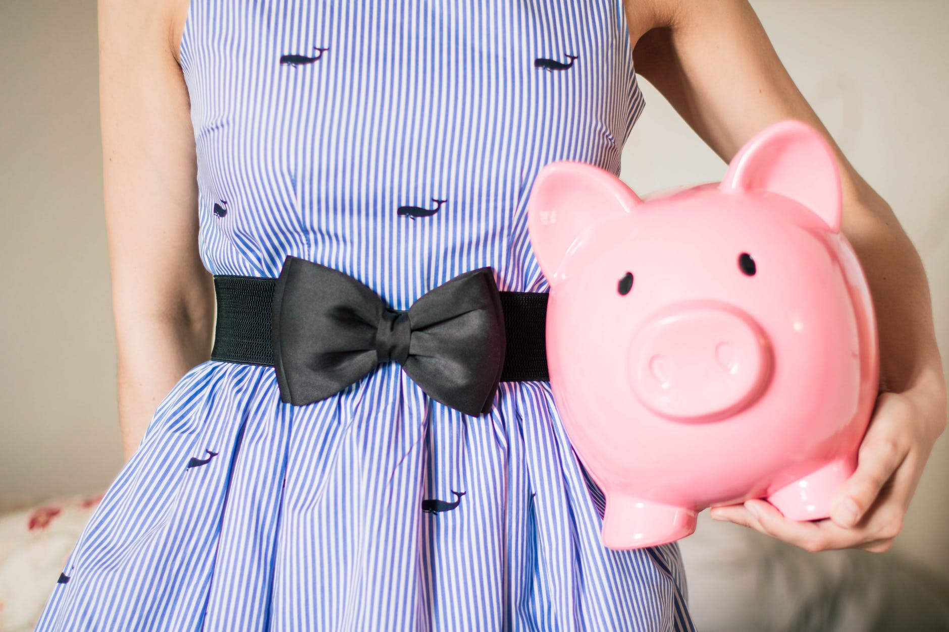 A woman in a blue dress holding a large piggy bank for saving money.