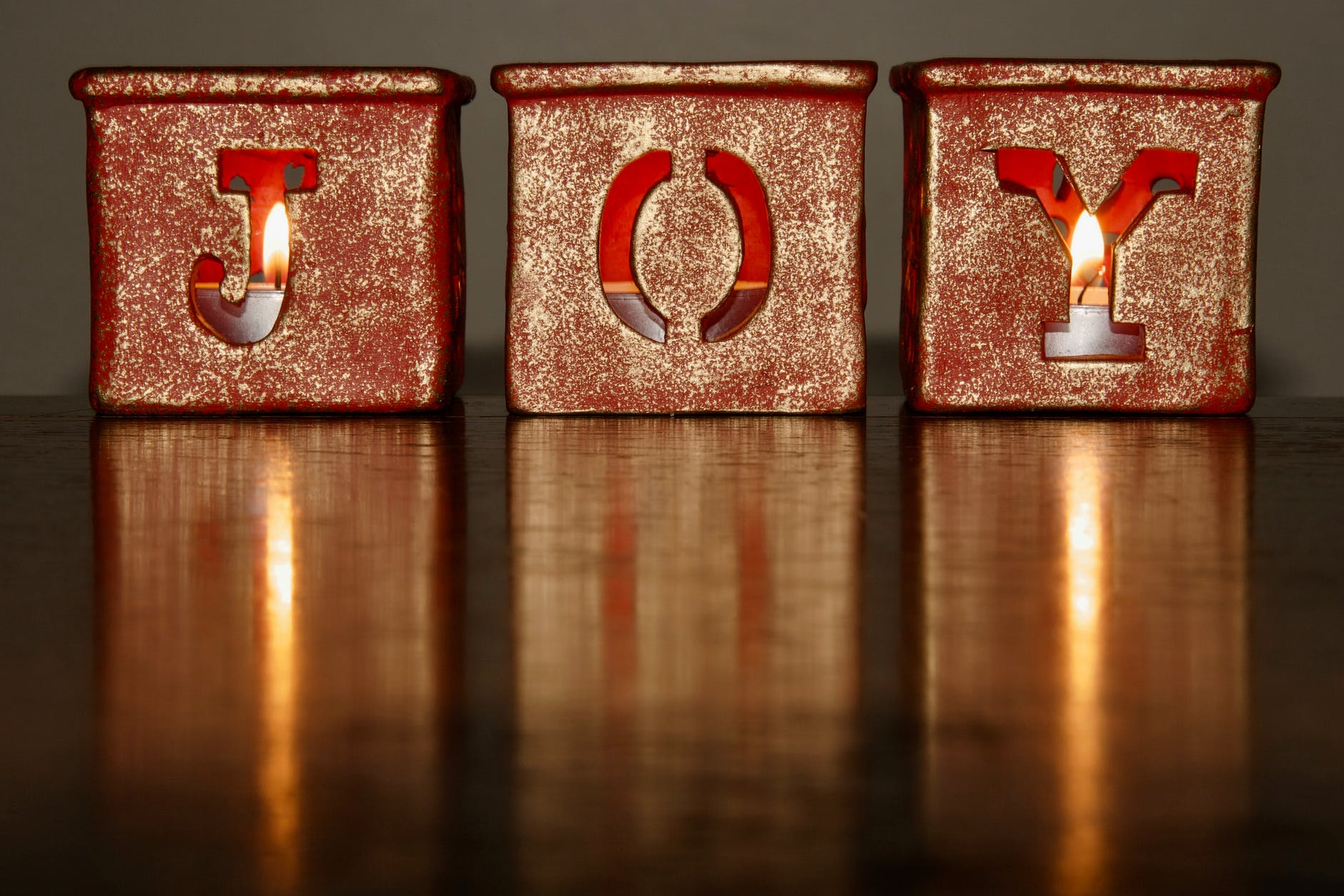 Photo of 3 festive candles which spell out joy