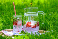 A jug and a glass of iced lemonade on a sunny lawn
