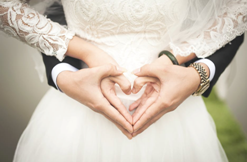 Bride and groom holding hands together in the shape of a heart
