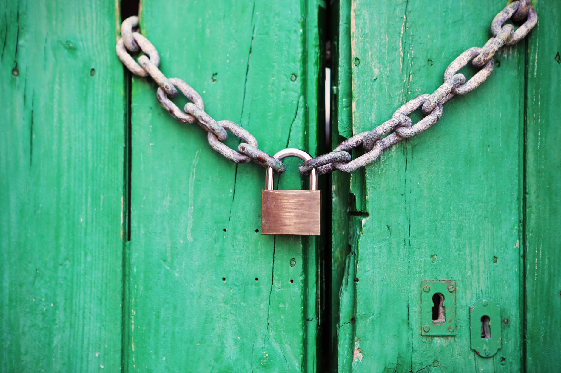 a chain and padlock holding green doors locked