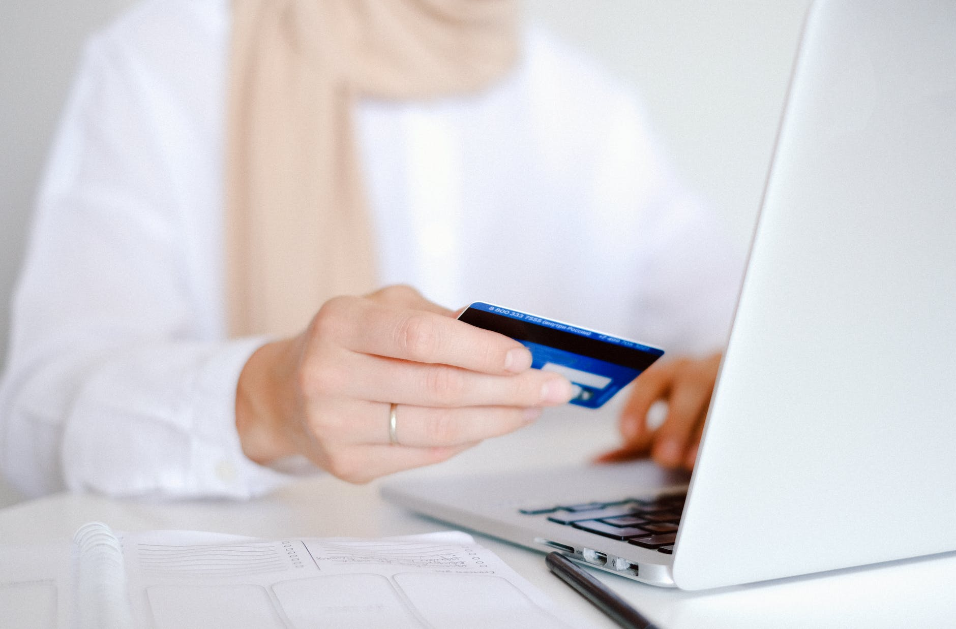 A woman in a white shirt about to make a payment with a debit card on her laptop.