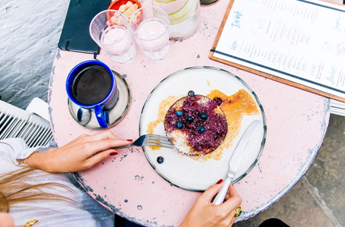 A woman at a restaurant eating blueberry pancakes with a cup of coffee and some water on her table