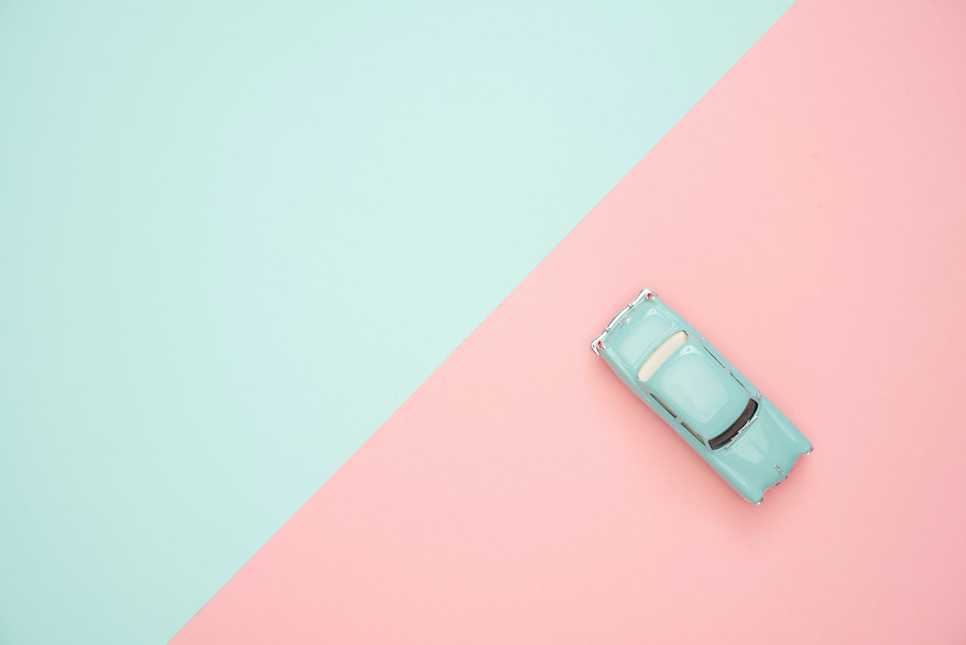 Blue and pink geometric photo with a small blue car